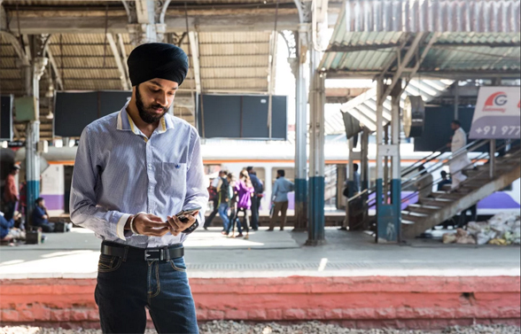 Young man standing on the platform at Mumbai train station looking at his phone