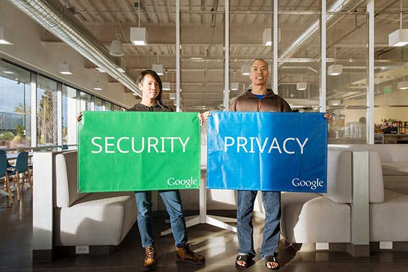 Two Google team members holding up a green security flag and blue privacy flag